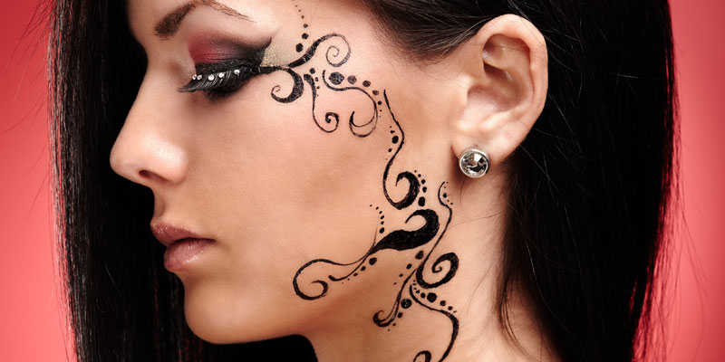 face henna tattoo with body jewelry